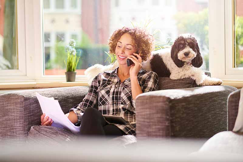 Woman sitting in chair, talking on phone, with dog behind her