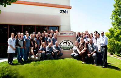 the staff of Rocklin Ranch Veterinary Hospital stading around the Rocklin Ranch Veterinary Hospital sign